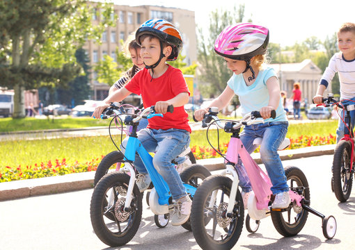 Cute little children riding bicycles outdoors on sunny day