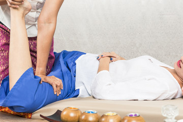 Young Girl get Thai style massage by Woman for body therapy