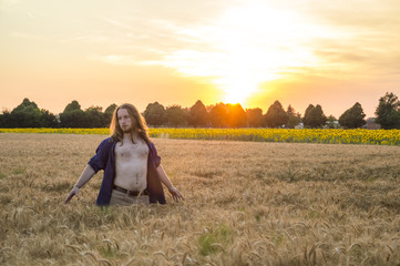 Young caucasian - nordic man with blond and long hairs among grain field at sunset