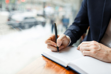 Businessman with pen making notes in notebook