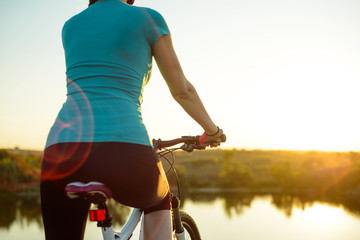 Young Woman Resting with Mountain Bike on Summer Rocky Trail and Looking at Beautiful Sunset. Travel, Sports and Adventure Concept.
