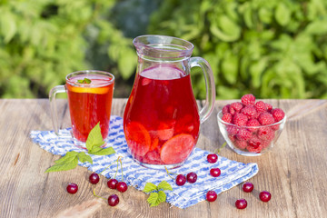 Dietary detox drink with lemon juice, red strawberry, cherry and raspberry in clear water with ice