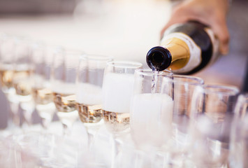 Bartender pouring champagne into glasses