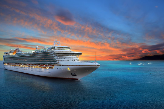 Luxury cruise ship sailing to port on sunrise