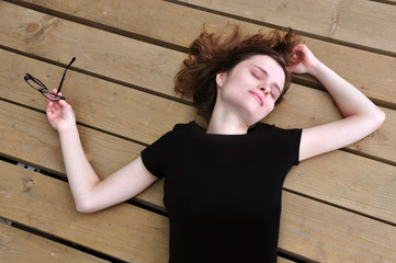 A young European girl lies and sleeps on a wooden surface. Black T-shirt mock up.