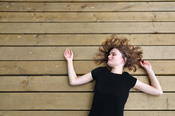 A young European girl lies and sleeps on a wooden surface. Black T-shirt mock up, empty space.