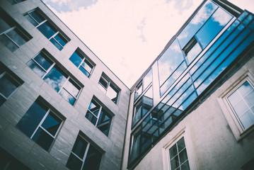 Sonne und Wolken spiegeln sich in Glasfassade eines Geschäftsgebäudes