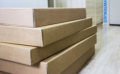 Pile of brown corrugated furniture box on laminate floor in living room at new condominium