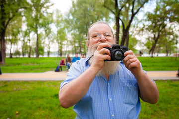 Old cheerful man with long beard making picture in park