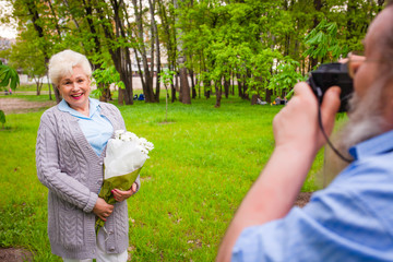 elderly man with a beard is making a photo of a wife with flower