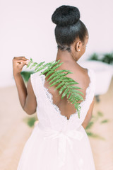 Beautiful african american bride with fern in the studio