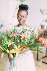 Beautiful african american bride with tropical bouquet in the studio