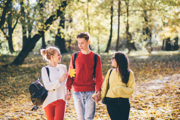 Education, lifestyle and people concept - young man in red shirt and two girls walking and talking in autumn park.
