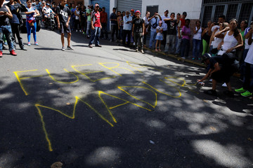 "People line up at a polling station as a man spray-paints ""Maduro Out"" on the pavement during an unofficial plebiscite against Venezuela's President Nicolas Maduro's government and his plan to rewrite the constitution, in Caracas"