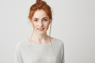 Portrait of beautiful tender ginger girl smiling posing looking at camera over white background.