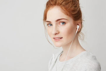 Portrait of young beautiful tender redhead girl with blue eyes in headphones looking at camera smiling over white background.