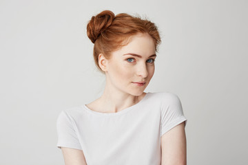 Portrait of playful beautiful young girl with red hair looking at camera over white background.
