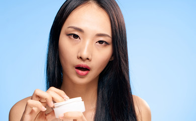 Beautiful young woman on blue background applies cosmetic face cream, asian