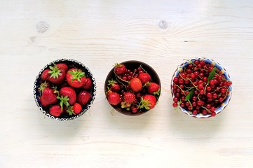 Fresh strawberries in a beautiful bowl on a white wooden table.