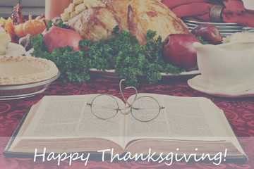 Bible and Holiday Dinner with Happy Thanksgiving Text