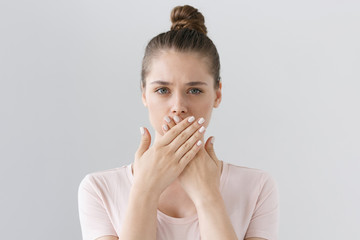Horizontal photo of young European female isolated on gray background with expression of secrecy and mistrust as she is covering mouth with two hands not willing to disclose something important.