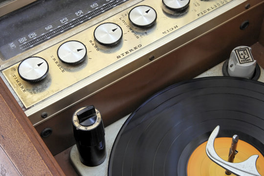 Vintage 1950 1960 hi-fi stereo radio console with lp record.