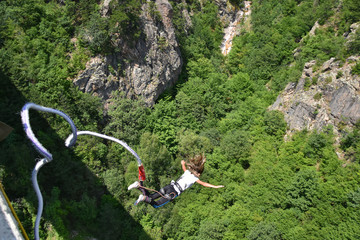 Bungee jumper girl with winded hair falling down from a 230-feet height bridge, rocks and green trees seen at the background