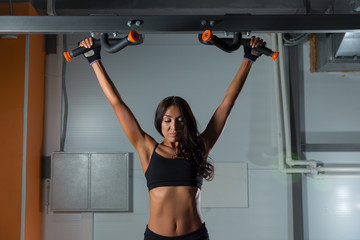 fitness girl exercises on horizontal bar in sport gym, back view. Active lifestyle.