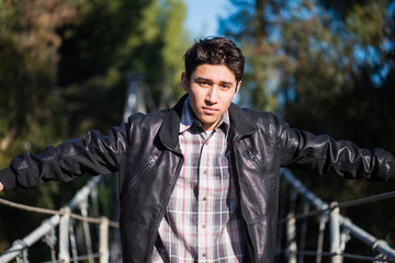 Young hispanic male sitting on a suspension bridge; posing, outdoors