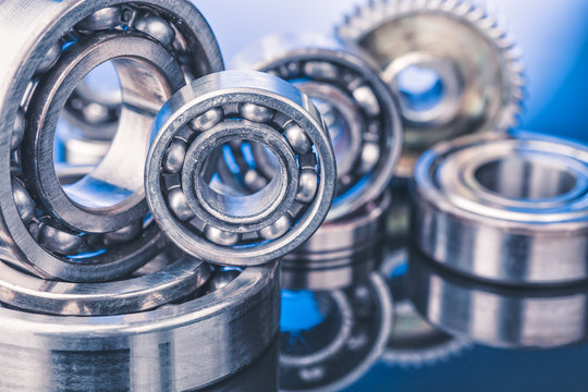Group of various ball bearings close up on nice blue background with reflections