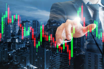 Double exposure of professional businessman pointing stock candles graph of stocks market on digital touch screen in business stock trading concept