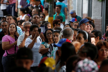 People line up to cast their votes at a polling station during an unofficial plebiscite against President Nicolas Maduro's government and his plan to rewrite the constitution, in Caracas