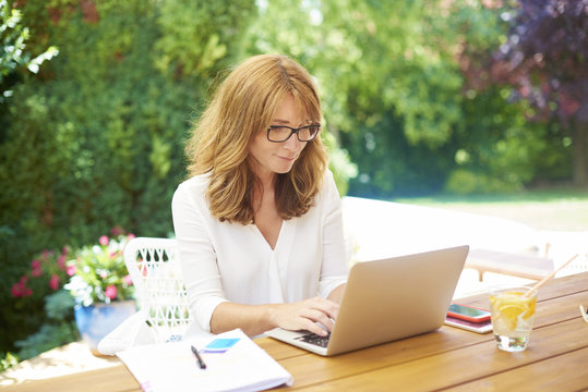 Home office is the best. Shot of a confident middle aged woman sitting at desk in garden and using laptop while working from home.