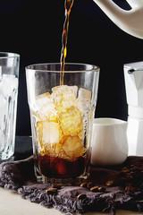 Iced coffee with milk. Summer drink. Dark background.