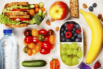 Healthy lunch box with sandwich and fresh vegetables, bottle of water and fruits