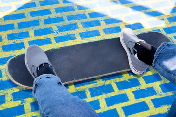 Stylish teenager boy wearing a checkered shirt and jeans on skateboard over colorful background