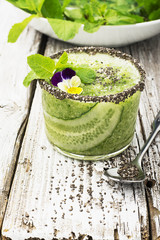 Fresh smoothies from cucumber, mint and honey in a glass are decorated with edible flowers of a garden viola. Selective focus.