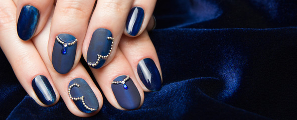 French manicure - beautiful manicured female hands with blue manicure with rhinestones on dark blue background, border design panoramic banner.