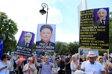 Protesters hold posters as they gather in front of the Parliament building during an opposition protest in Warsaw