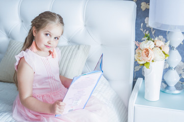 Little girl is sitting on the bed and reading a book