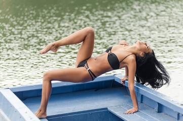 beautiful girl posing in a boat in a swimsuit