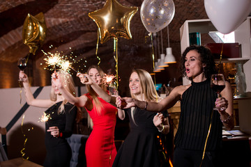 Happy pretty young women holding firework sparklers, balloons, glasses of wine celebrating a holiday in restaurant with Gothic interior