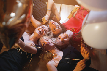 Laughing young women looking down into camera holding balloons having party