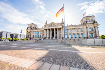 Fototapete - View on the famous Reichtag parliament building with flag during the morning light in Berlin city