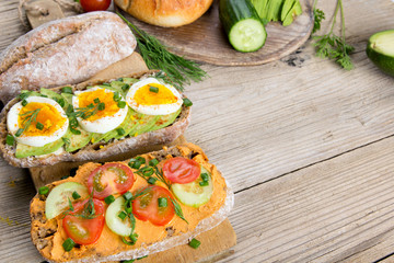 Sandwiches with avocado, eggs and tomato on a wooden background. Fresh organic vegetables, eggs and whole wheat bread. Healthy breakfast. Retro style.