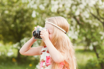 Portrait of a cute girl on photographing beautiful retro camera