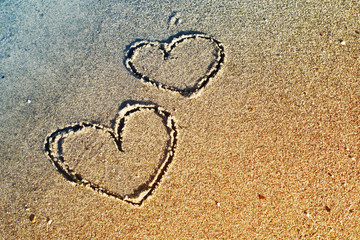 Two hearts are drawn on sea sand, toned.  Romantic card. Declaration of love. Gift by St. Valentine's Day.