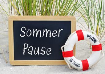 Sommerpause - Kreidetafel mit Rettungsring am Strand - Sommerurlaub, Betriebsferien, Sommerferien