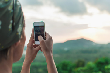 Young woman standing taking a picture of the sunset landscape