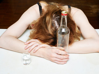 Drunk girl sleeps at the table. Women's alcohol dependence.